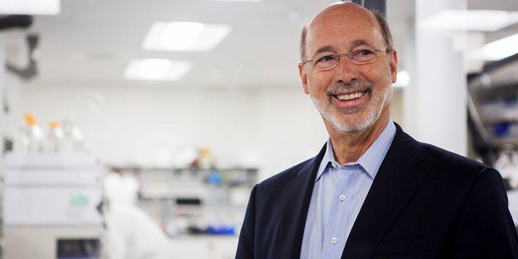 Image of Governor Wolf smiling next to a lab