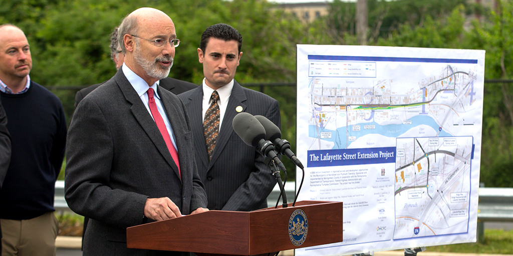 Image of Governor Wolf speaking next to a map