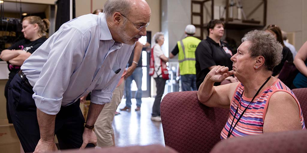 Image of Governor Wolf speaking to a displaced resident following CSX derailment.