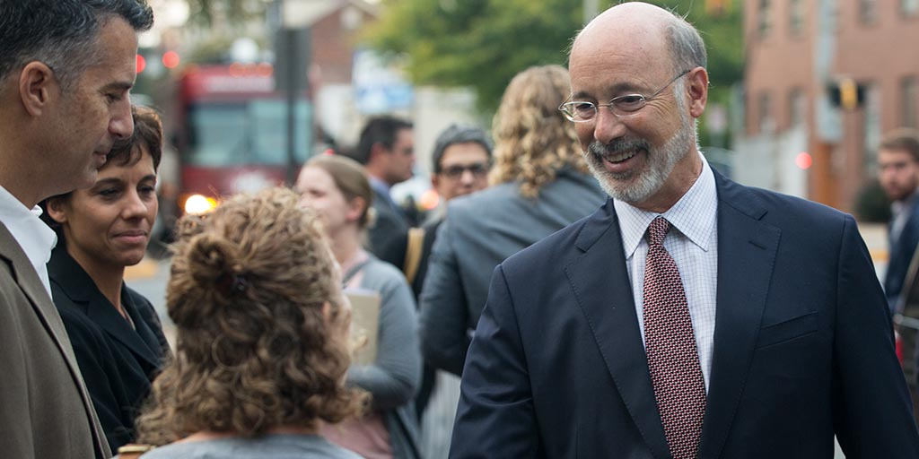 Image of Governor Wolf greeting someone on the street