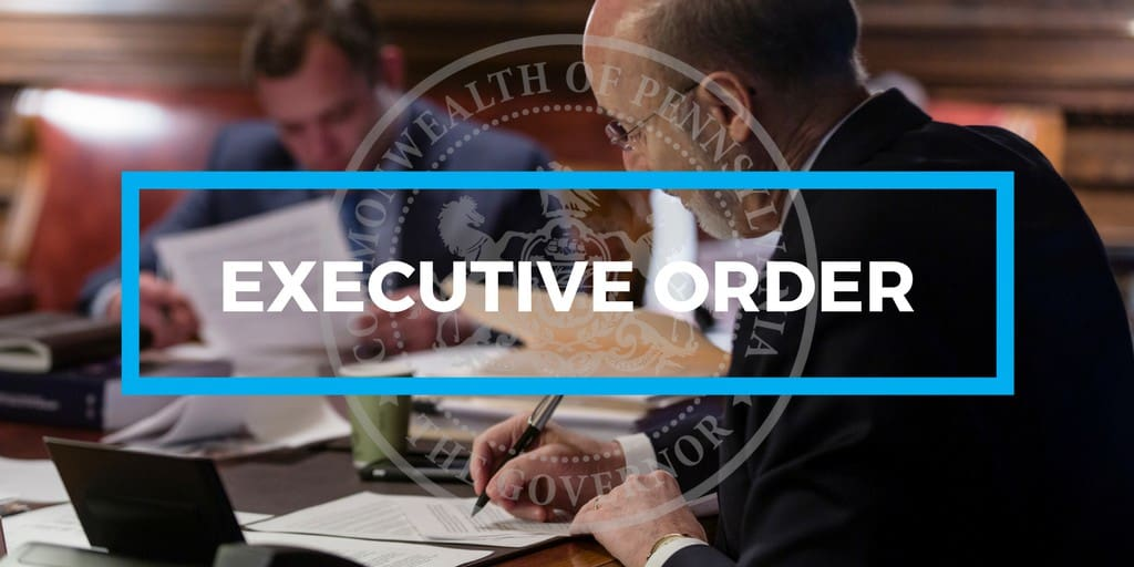 Governor Tom Wolf signs an executive order at his desk