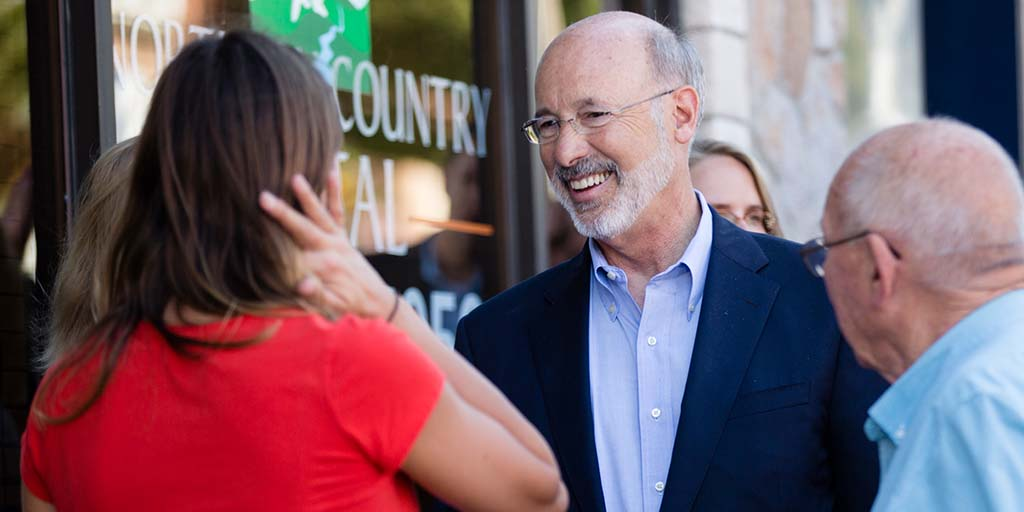 Image of Governor Wolf meeting people in front of a small business