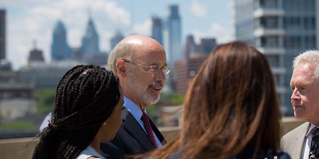 Image of Governor Wolf speaking to a group of people in front of the Philadelphia skyline.