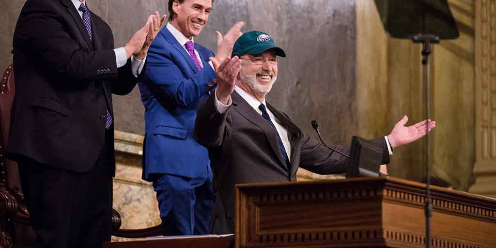 Image of Governor Tom Wolf wearing a Philadelphia Eagles hat with his arms raised.