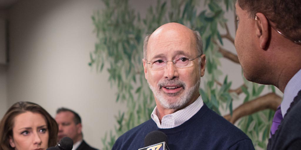 Image of Governor Tom Wolf standing in front of a tree mural.