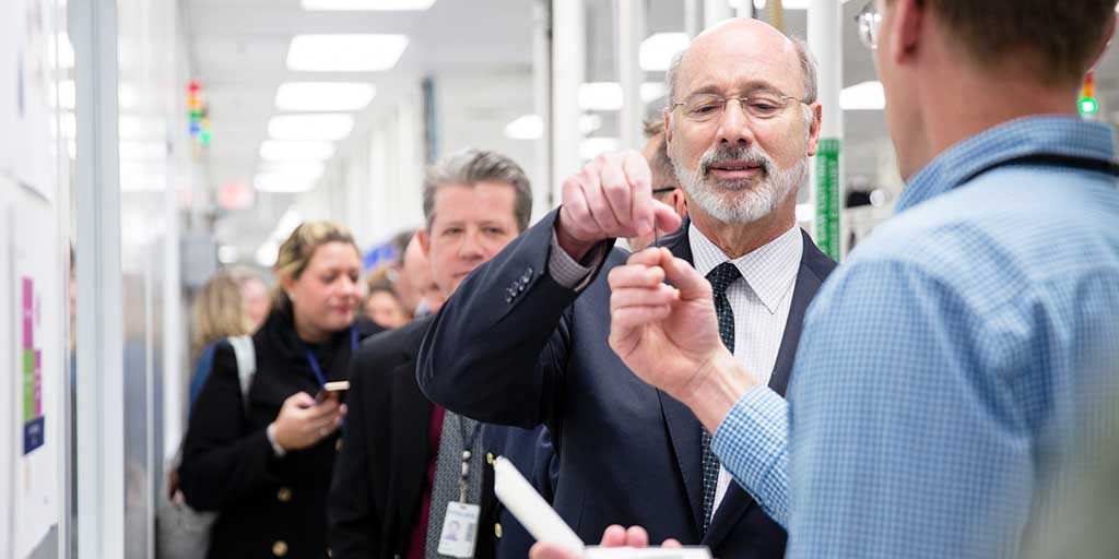 Image of Governor Tom Wolf inspecting an item.