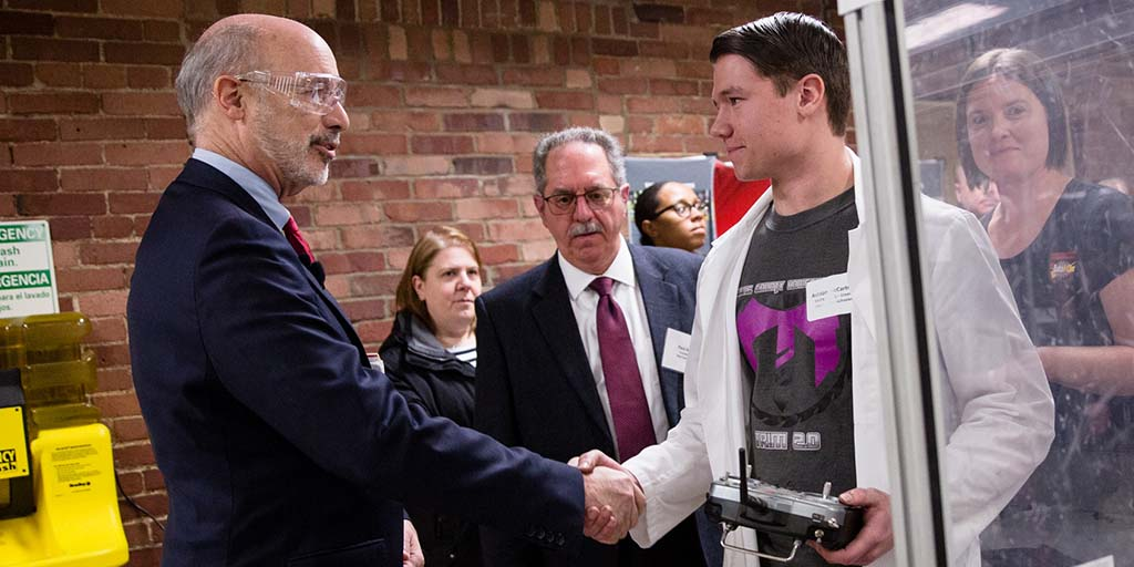 Image of Governor Tom Wolf shaking hands with a person wearing a lab coat.