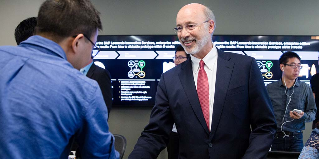 Image of Governor Tom Wolf greeting people in front of a large screen