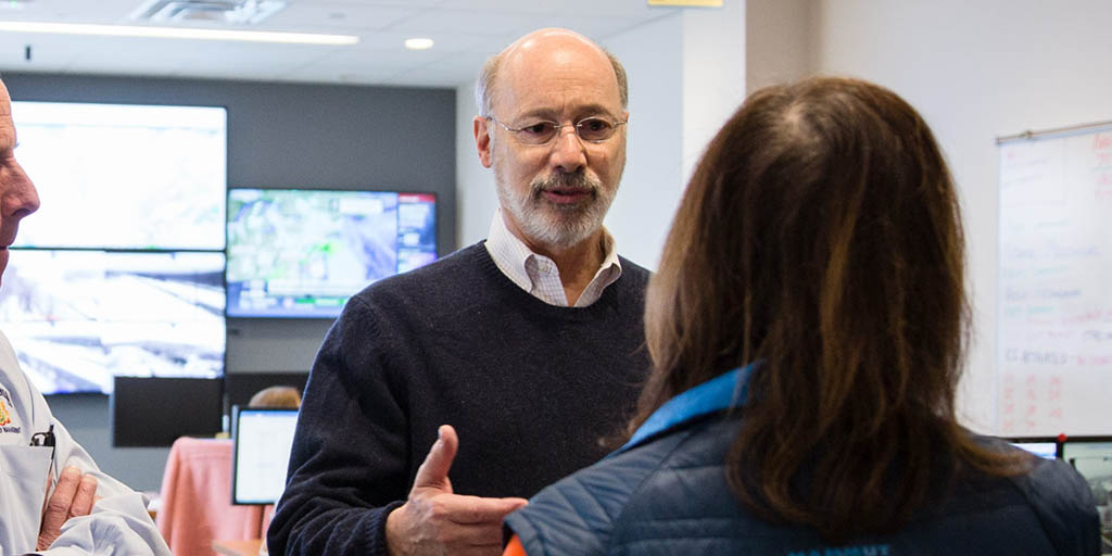 Image of Governor Tom Wolf speaking to someone in front of large screens.