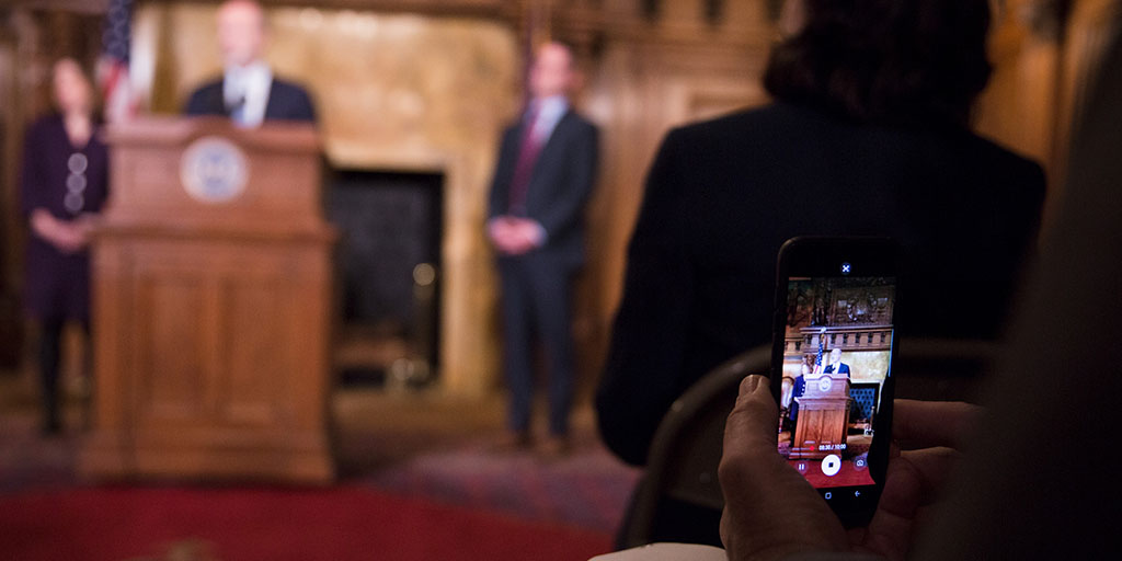 Close up image of a cell phone recording Governor Tom Wolf during broadband announcement.