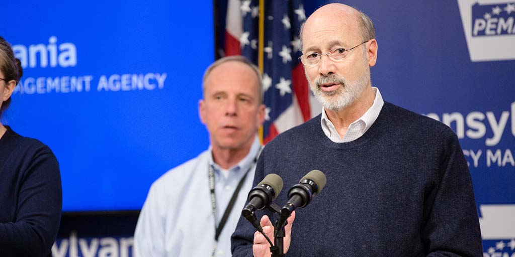 Image of Governor Tom Wolf speaking in front a blue backdrop and standing next to the director of PEMA.