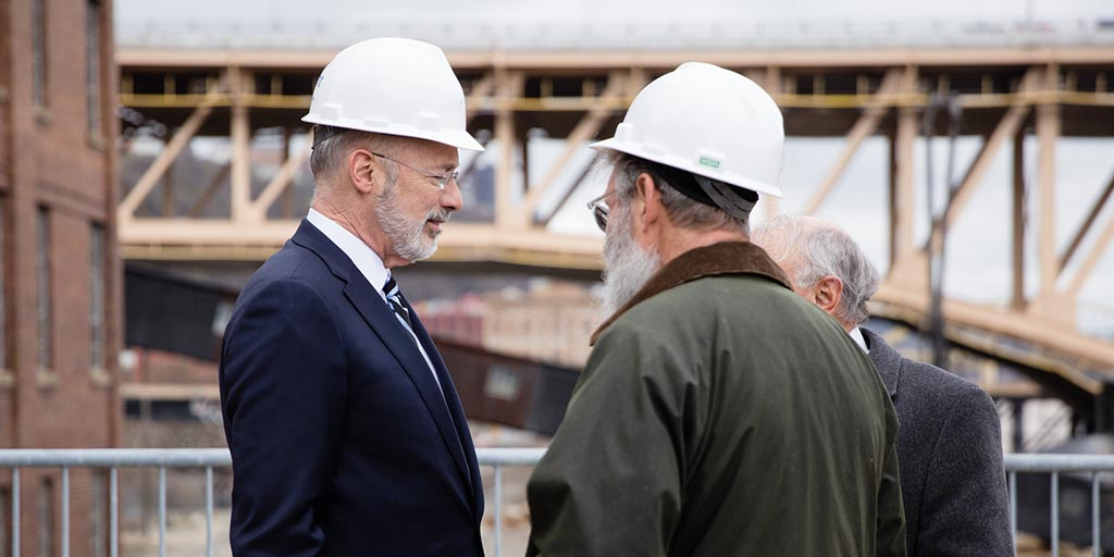 Image of Governor Tom Wolf wearing a hardhat and speaking to people next to a construction site.