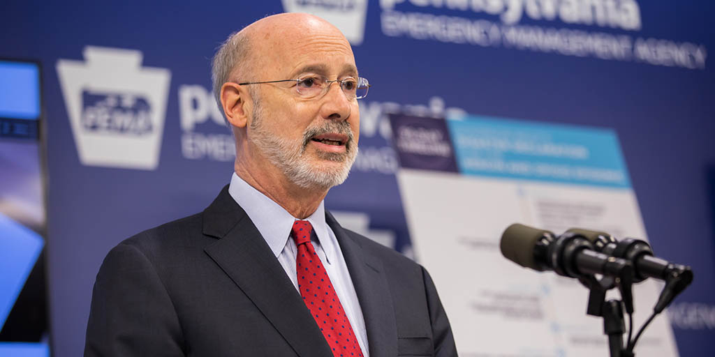 Image of Governor Tom Wolf speaking next to an opioid disaster declaration timeline poster.