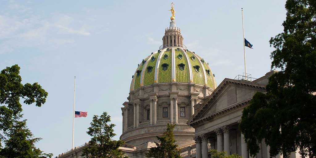 Image of the US and PA flag at half-staff.
