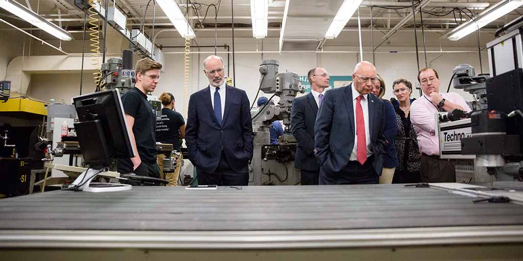 Image of Governor Tom Wolf inspecting manufacturing equipment.