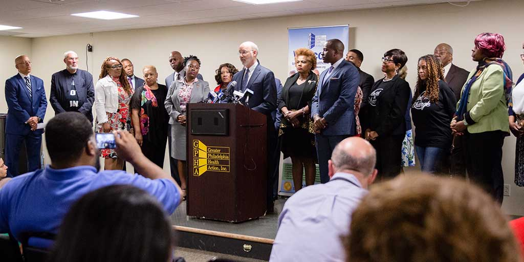 Image of Governor Tom Wolf speaking from a stage and accompanied by community leaders and legislators.