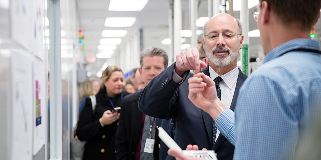 Image of Governor Tom Wolf inspecting an object.