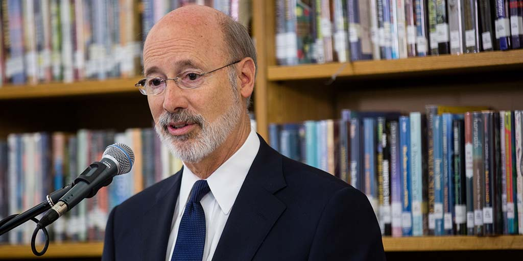 Image of Governor Tom Wolf providing remarks in front of a bookshelf.