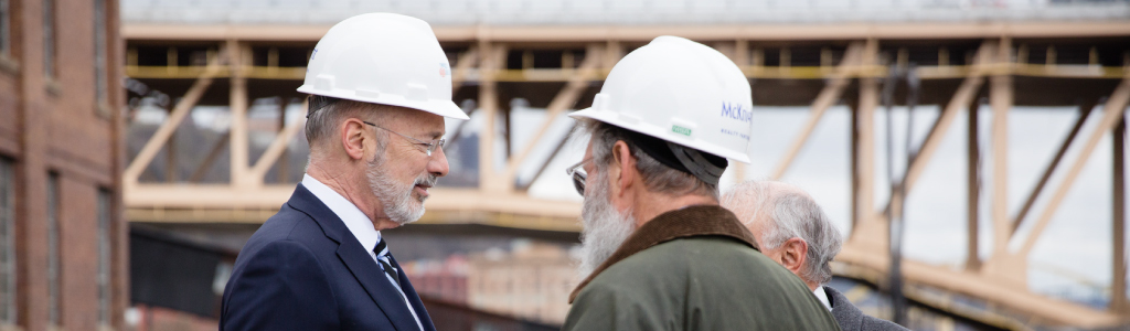 Image of Governor Tom Wolf wearing a construction hat and standing next to a bridge.