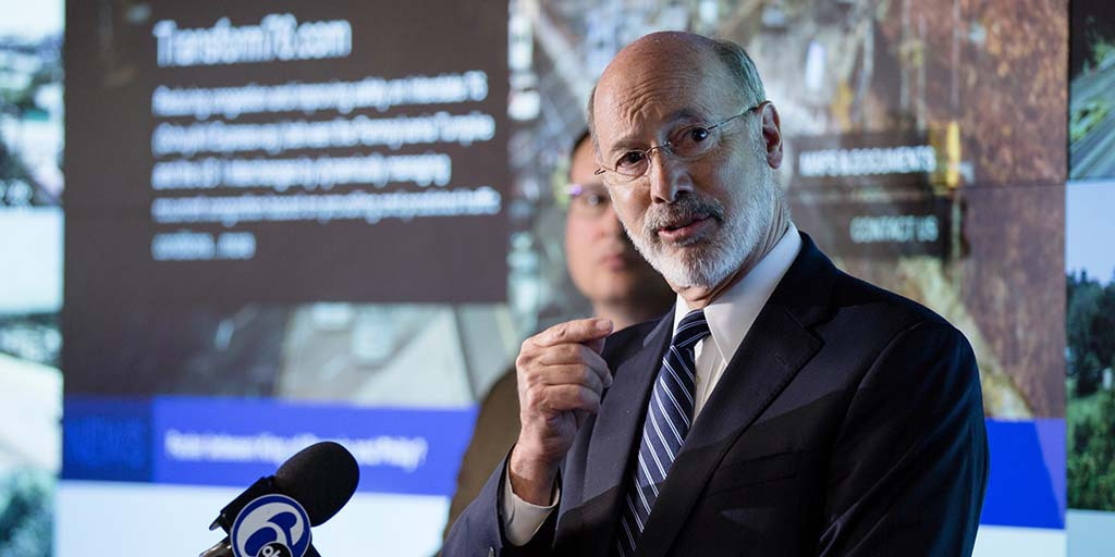 Image of Governor Tom Wolf speaking in front of a large wraparound screen.