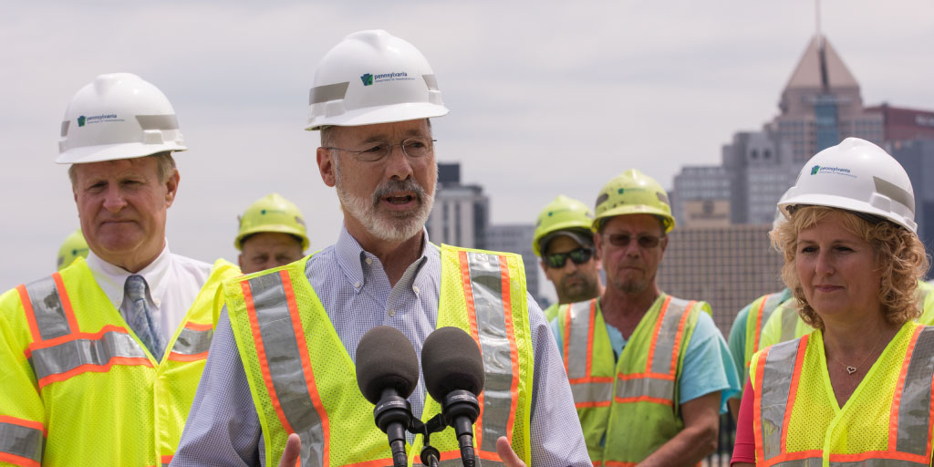 Image of Governor Tom Wolf providing remarks in front of the Pittsburgh skyline.