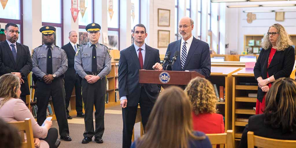 Image of Governor Tom Wolf speaking from behind a podium inside a school library.