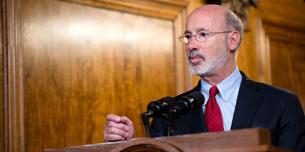 Governor Tom Wolf speaks behind a podium.