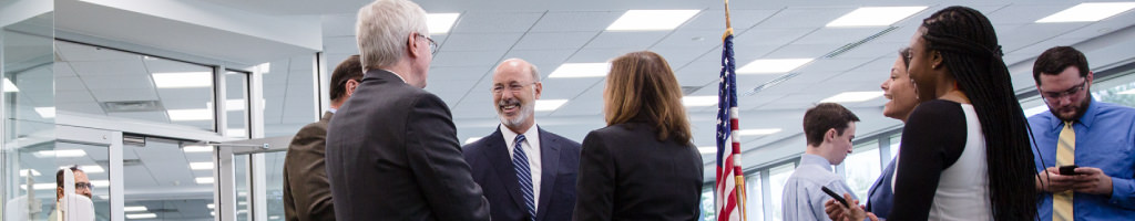 Image of Governor Tom Wolf interacting with officials and staff in an office.