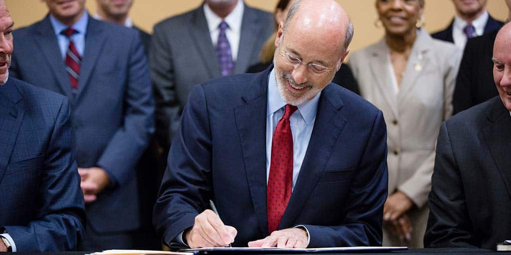 Image of Governor Tom Wolf signing an executive order.