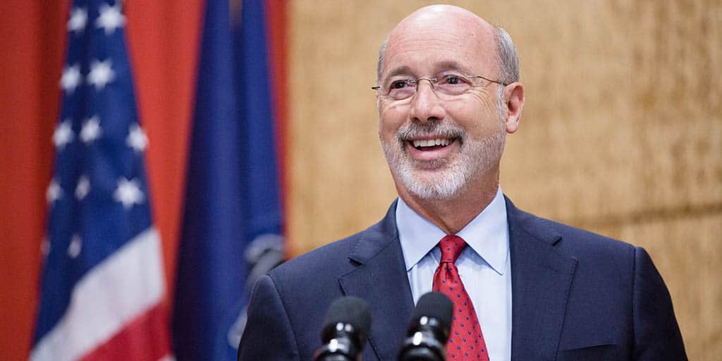 Image of Governor Tom Wolf smiling next to the PA and U.S. flags.
