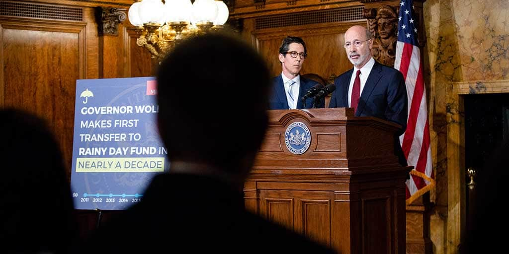 Image of Governor Tom Wolf speaking behind a podium joined by Pennsylvania Treasurer Joe Torsella.