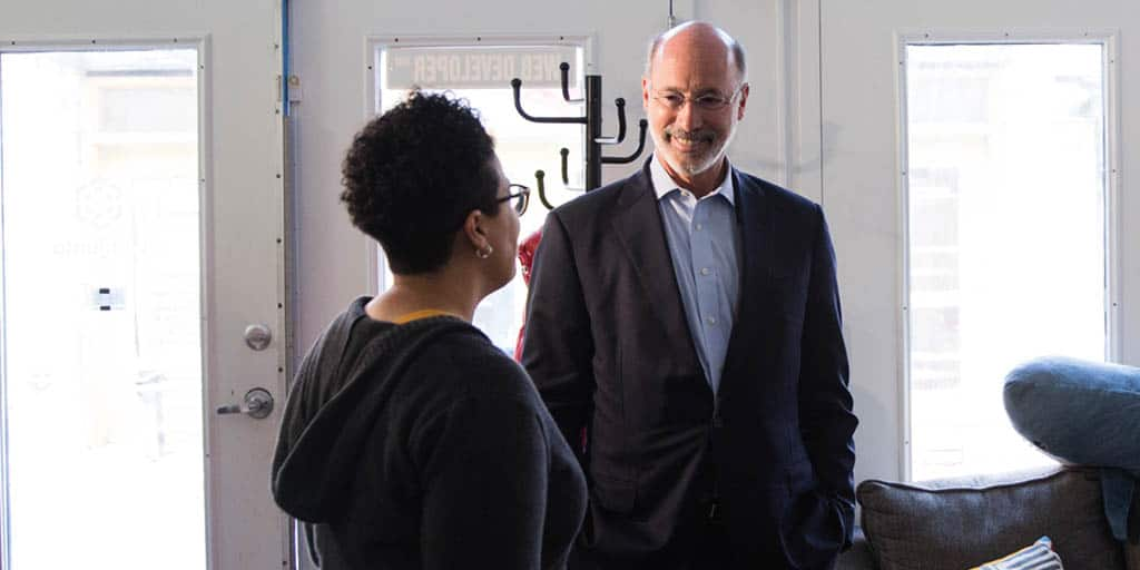 Image of Governor Tom Wolf speaking to a CEO.