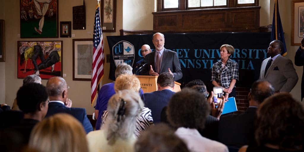 Image of Governor Tom Wolf speaking in a grand hall.