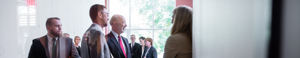 Governor Tom Wolf being greeted in a hallway.
