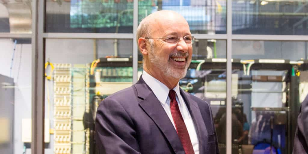 Close up image of Governor Tom Wolf standing in front of a glass wall.