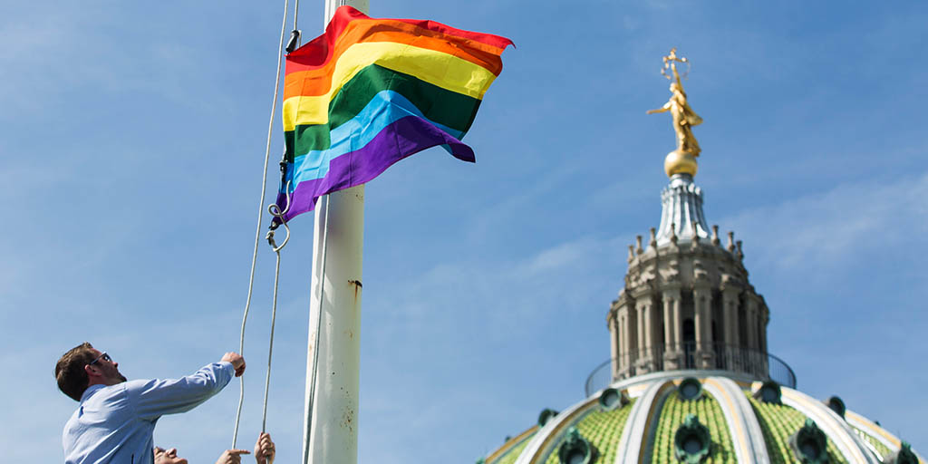 Image of an LGBTQ flag being raised at the Pennsylvania Capitol Building.