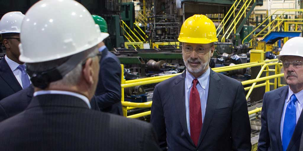 Image of Governor Tom Wolf standing next to large manufacturing equipment.