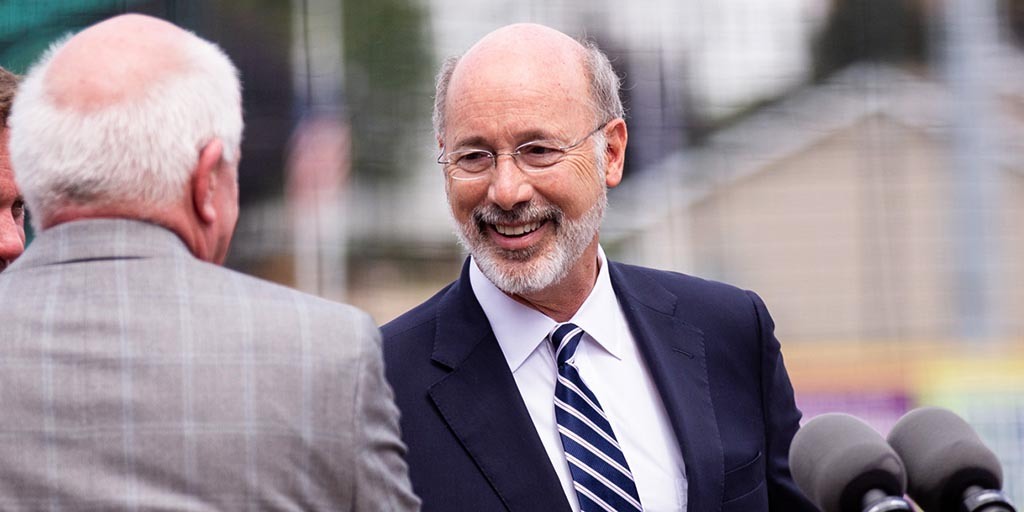Image of Governor Tom Wolf shaking hands with someone outside.