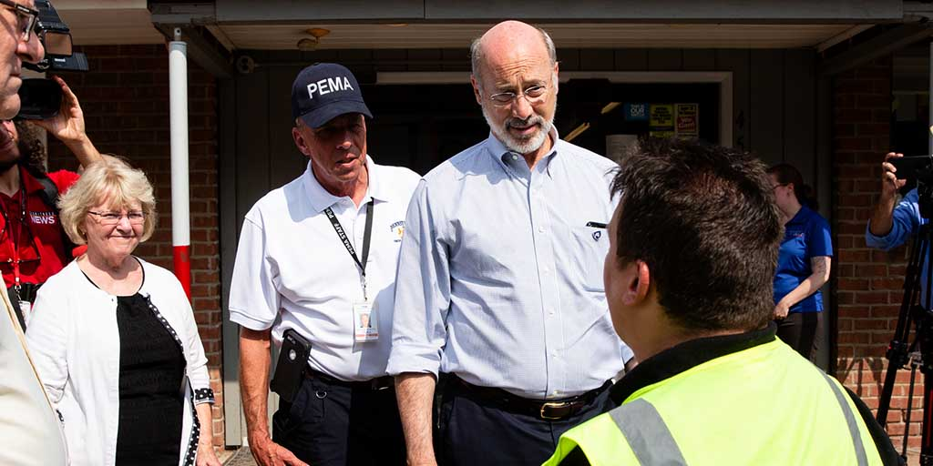 Image of Governor Tom Wolf speaking to a disaster cleanup volunteer.