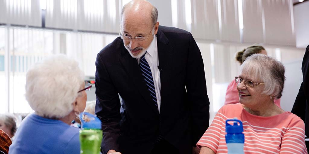 Image of Governor Tom Wolf speaking to seniors who are sitting at a table.