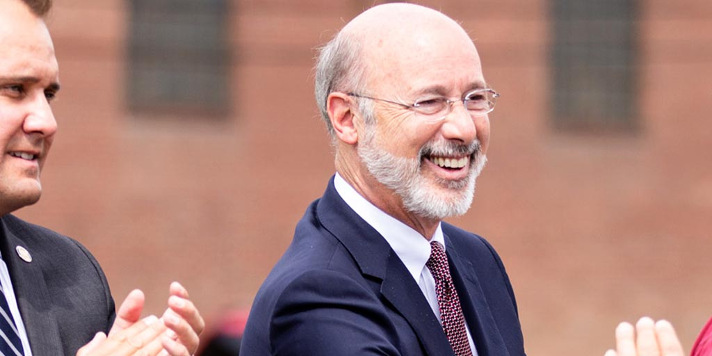 Image of Governor Tom Wolf smiling and greeting people near a brick wall.