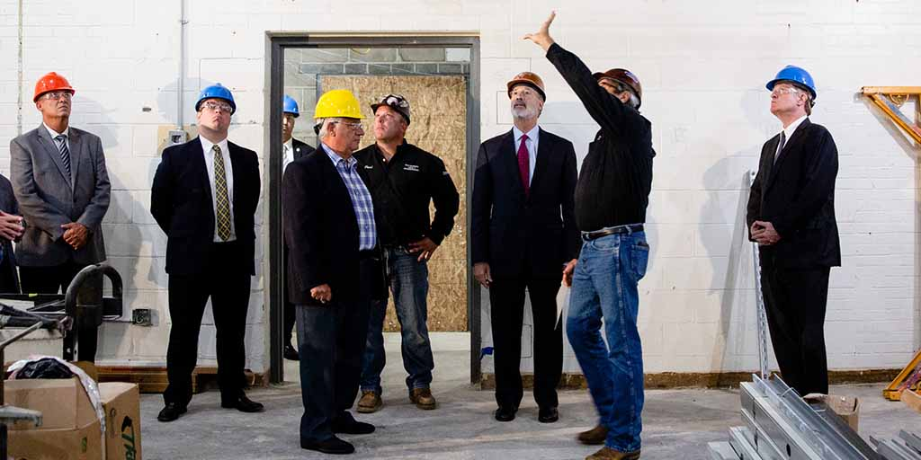 Image of Governor Tom Wolf and construction workers inspecting a ceiling.