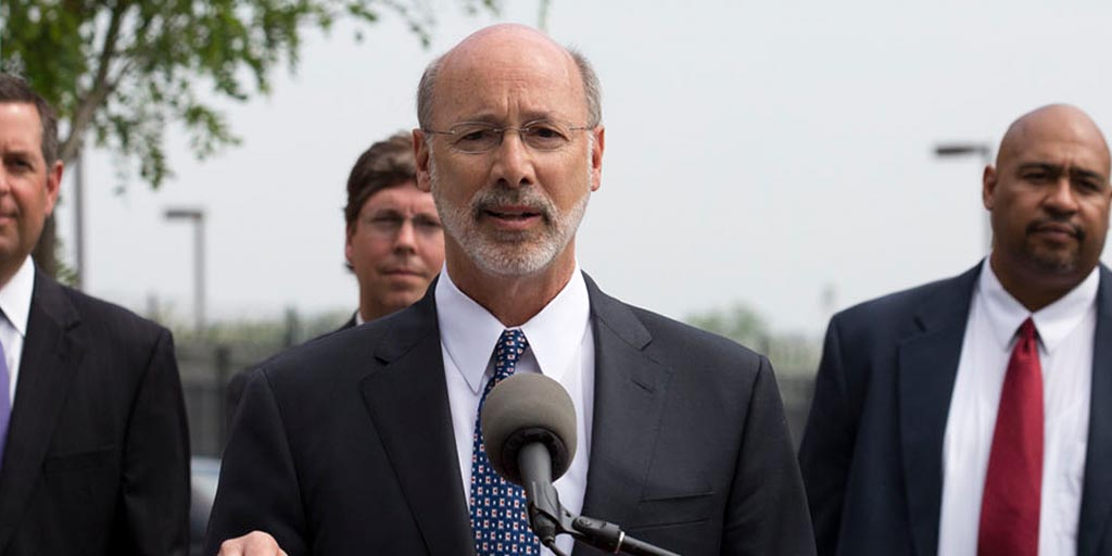Image of Governor Tom Wolf speaking behind a podium outside.