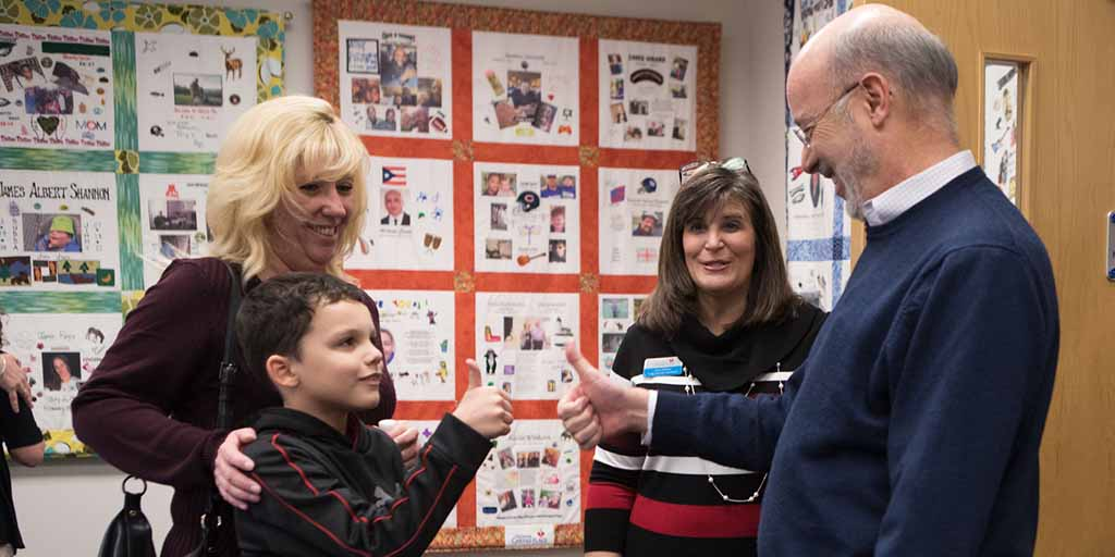 Image of Governor Tom Wolf giving a thumbs-up to a child who is also doing the same.