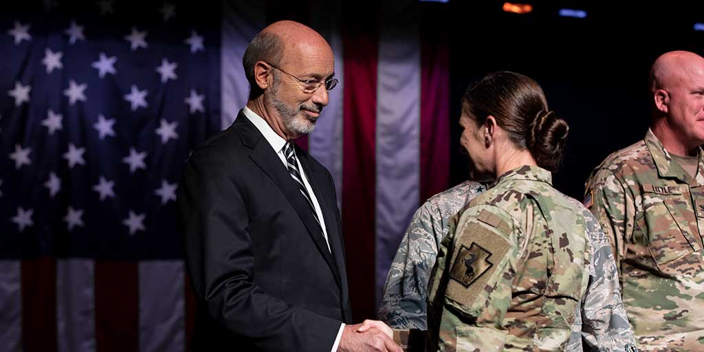 Image of Governor Tom Wolf speaking shaking hands with a soldier.