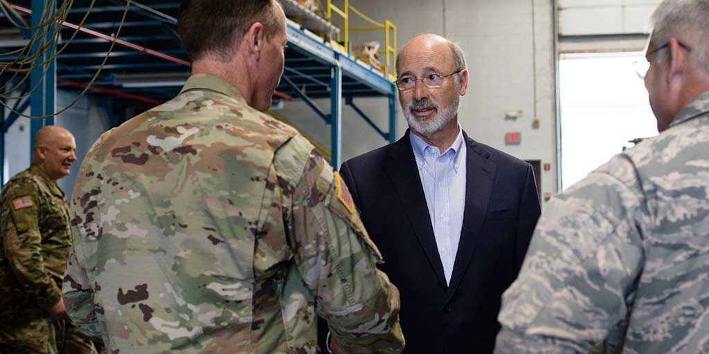 Image of Governor Tom Wolf speaking to a member of the National Guard.