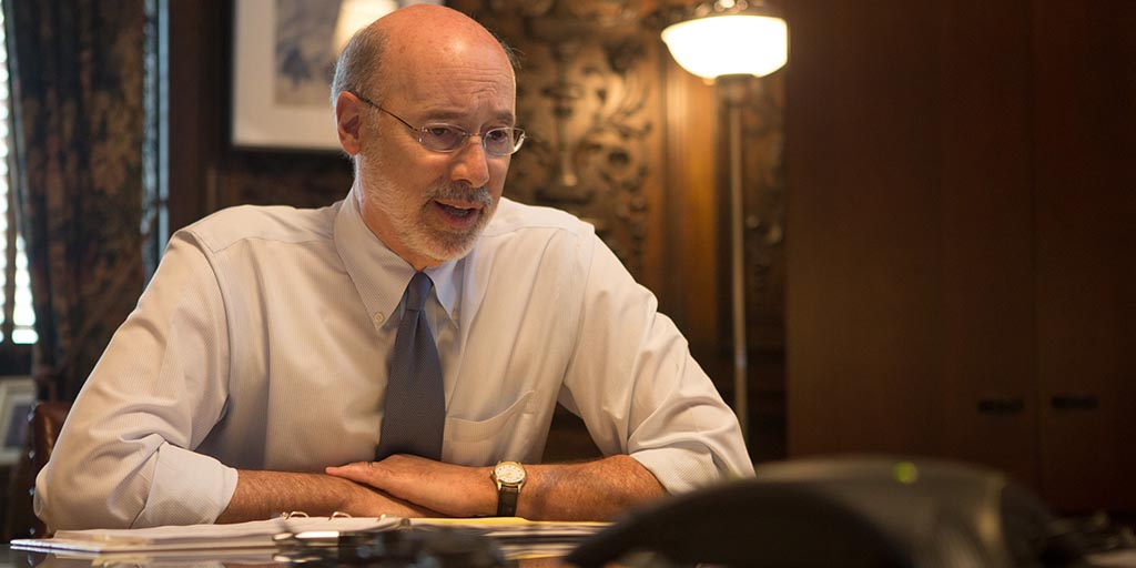 Image of Governor Tom Wolf speaking to a phone during a conference call.