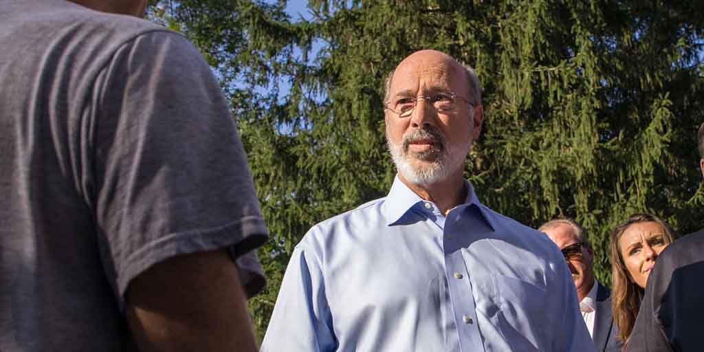 Image of Governor Tom Wolf standing next to a tree and speaking to a group of people.