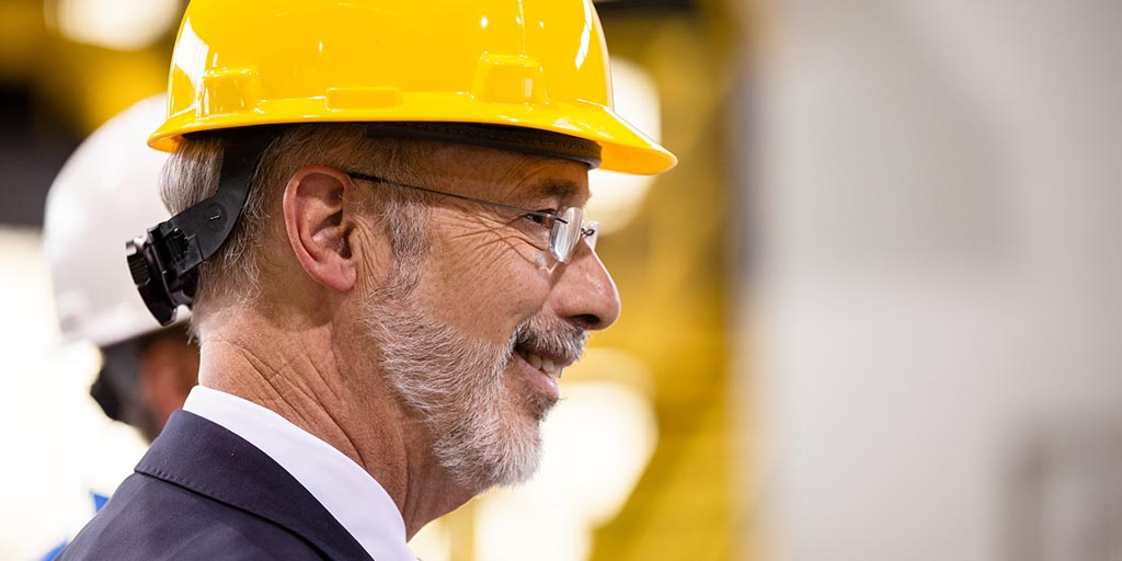 Image of Governor Tom Wolf smiling and wearing a hard hat.