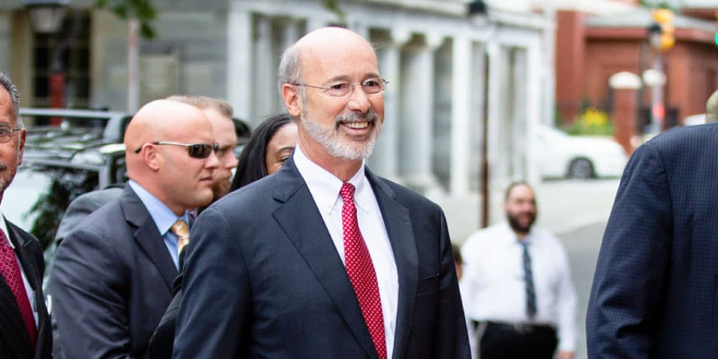 Image of Governor Tom Wolf walking across a downtown street.